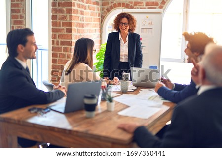 Group of business workers smiling happy and confident in a meeting. Working together looking at presentation using board and charts at the office.