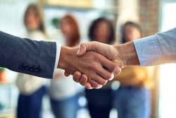 Group of business workers standing together shaking hands at the office