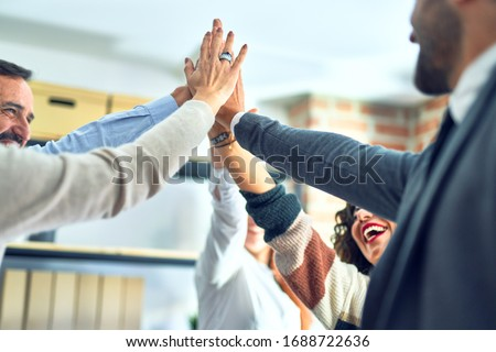 Group of business workers standing with hands together highing five at the office Photo stock ©