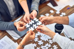 Group of business workers with hands together connecting pieces of puzzle at the office