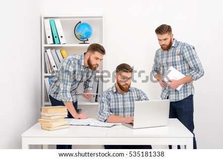 Group of businessman clones working together at the office, using laptop and tablet computer