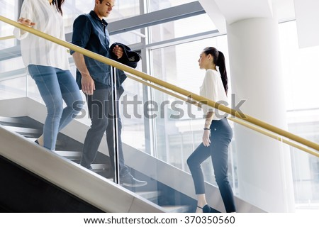 Group of businessman walking and taking stairs in an office building