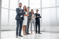 group of businessmen and businesswoman standing in an office with a large window