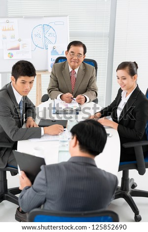 Group of businessmen sitting and looking at colleague