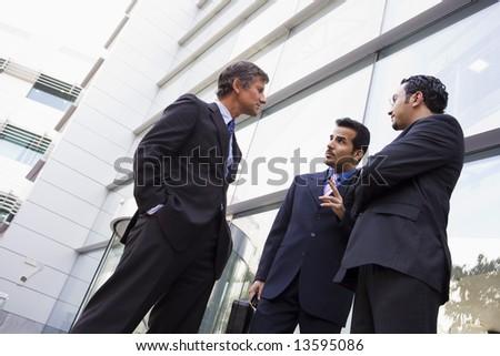 Group of businessmen talking outside modern office building