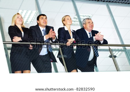 Group of businesspeople and their senior boss standing by banisters