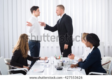 Group Of Businesspeople Looking At Businessman Blaming His Colleague In Meeting #427553626
