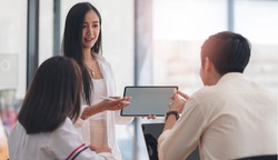 Group of businesspeople meeting and discussing about business plan in modern office, young businesswoman using tablet presenting business plan with her team in office.