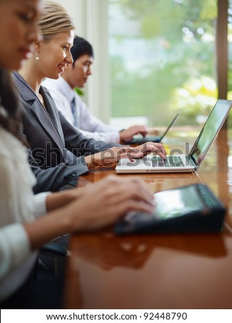 Group of businesspeople meeting in conference room and using laptop computers. Side view, copy space