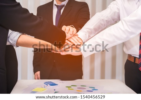 Group of businesspeople putting stacking hands while meeting for showing unity of teamwork. Business and teamwork concept.