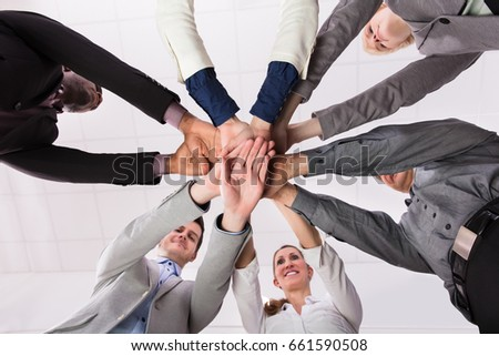 Group Of Businesspeople Putting Their Hands On Top Of Each Other Against White Background #661590508