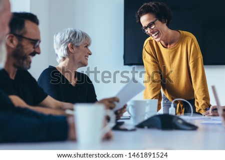 Group of businesspeople smiling during a meeting in conference room. Business people having casual discussion during meeting in board room.
