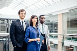 group of businesspeople standing together in office and looking at camera