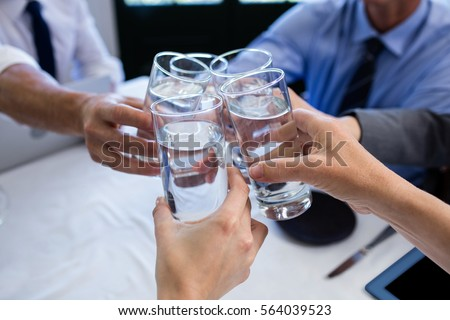 Group of businesspeople toasting glass of water during business meeting in restaurant