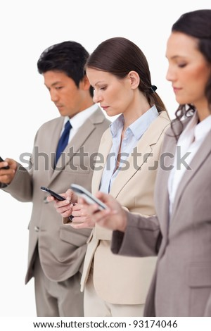 Group of businesspeople with their cellphones against a white background