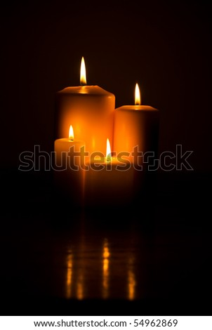 Group of candle lights on a wood table with reflection in darkness