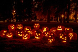Group of candle lit carved Halloween pumpkins in park on fall evening