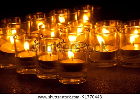 Group of candles in glass .
