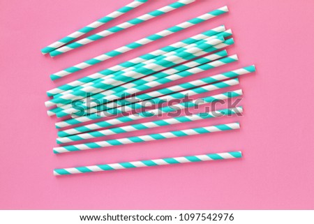 Group of cardboard tubes for cocktails with blue striped straws on a pink table. Selected focus. Top view.