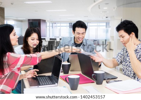 Group of casually dressed business people working together in the office #1402453157