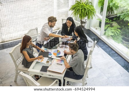 Group of casually dressed businesspeople discussing ideas in the office. Creative professionals gathered at the meeting table for discuss the important issues of the new  #694524994