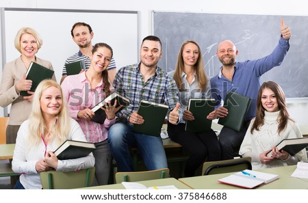 Shutterstock Group of cheerful adult students and coach posing at training session school. Selective focus