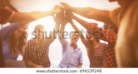 Group of cheerful business people giving high five while sitting creative office #696539248