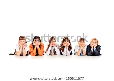 Group of cheerful children lying on a floor together. Isolated over white.