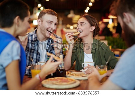 Group of cheerful friends eating delicious pizza and chatting animatedly while gathered in lovely small cafe, waist-up portrait
