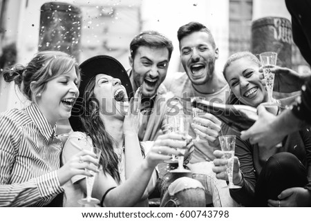Group of cheerful friends having a party in the city throwing confetti and drinking champagne - Beautiful young people laughing having fun on the street drinking  prosecco celebrating a birthday