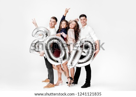 Group of cheerful friends of two girls and two guys dressed in stylish clothes are holding balloons in the shape of numbers 2019 on a white background in the studio #1241121835
