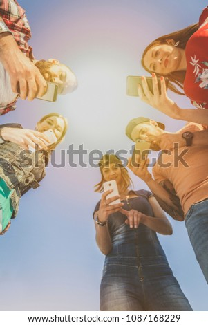 group of cheerful friends takes photos with smart phones. capture from below againt sunlight. happy people stream a story on social media community. millenial generation concept.