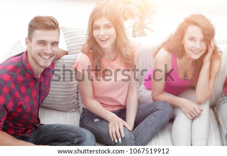 group of cheerful friends watching videos, sitting on the couch #1067519912