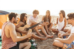 Group of cheerful happy friends camping at the beach, drinking beer, laughing, playing guitar