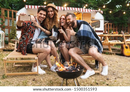 Group of cheerful happy friends sitting at the trailer outdoors, having a picnic with bonfire, taking a selfie