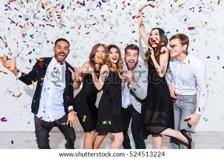 Group of cheerful joyful young people standing and celebrating together over white background