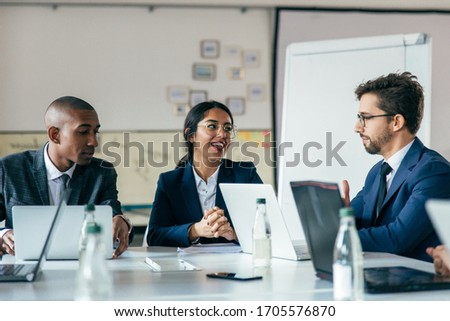 Group of cheerful managers communicating during meeting. Smiling young business people talking during briefing. Business meeting concept