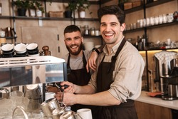 Group of cheerful men baristas wearing aprons working at the counter in cafe indoors, talking