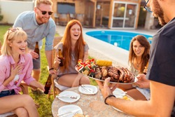 Group of cheerful young friends gathered around the table, drinking beer and having fun at a backyard poolside barbecue party, host bringing plate of grilled meat and vegetables