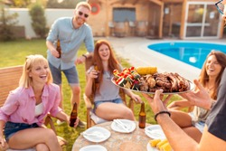 Group of cheerful young friends gathered around the table, drinking beer and having fun at backyard poolside barbecue party while the host is serving food