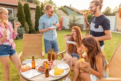 Group of cheerful young friends gathered around the table, eating grilled meat, drinking beer and having fun at a backyard barbecue party