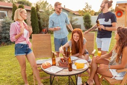 Group of cheerful young friends gathered around the table, eating grilled meat, drinking beer and having fun at backyard barbecue party