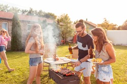 Group of cheerful young friends having a backyard barbecue party, grilling meat, drinking beer, playing badminton and relaxing on a sunny summer day outdoors