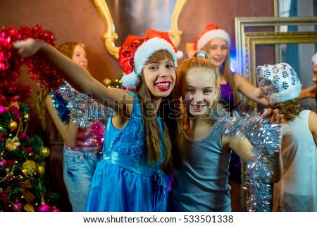 Group of cheerful young girls celebrating Christmas near the Christmas tree with lights #533501338