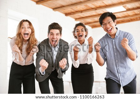 Group of cheerful young multiethnic businesspeople looking at camera and celebrating success