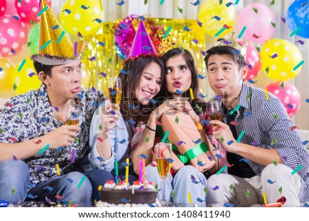 Group of cheerful young people taking selfie picture together with funny expression at a birthday party
