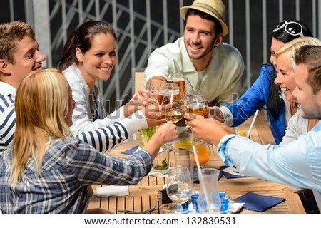 Group of cheerful young people toasting with drinks night out