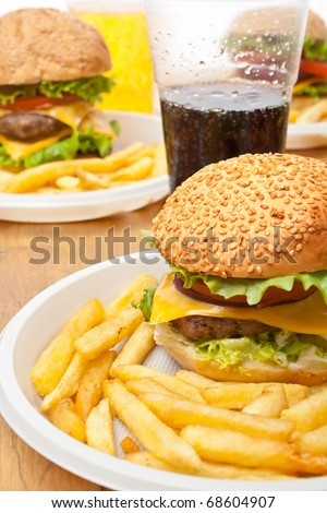 group of cheeseburgers with french fries and drinks on  a wooden table