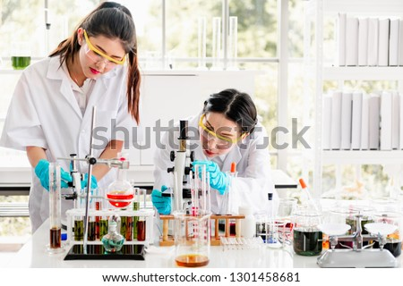 Group of chemists working in a lab. Young asian female chemists with senior caucasian chemist working together in lab, looking into microscope. Science concept.