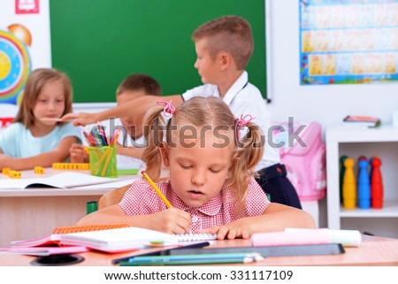 Group of children at the desks in classroom